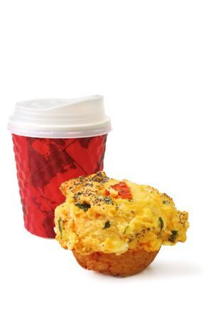 Take-out coffee with a savory muffin, isolated on white.  Breakfast or a snack when youre in a hurry.  Muffin has spinach, sundried tomatoes, and poppy seeds.