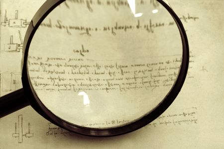 Historical research ~ magnifying glass over page of Leonardo Da Vincis mirror-writing and technical drawings.