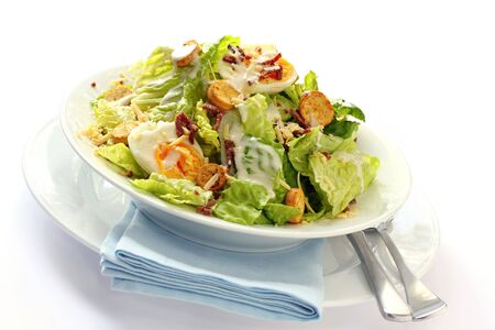 Caesar salad in a white bowl with blue napkin.  Delicious eating. photo