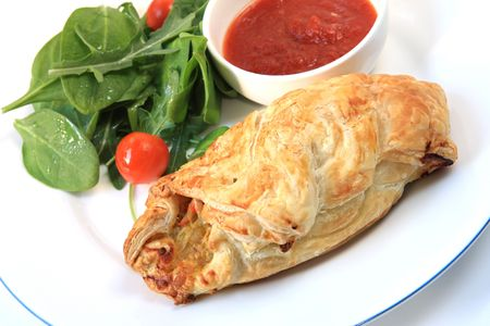 cornish: Cornish pasty and salad, with a chili dipping sauce.  A modern variation on this traditional Cornish miners vegetable pie. Stock Photo