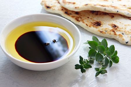 balsamic: Oil and vinegar - small bowl of olive oil and balsamic vinegar, with dipping bread and fresh herbs.