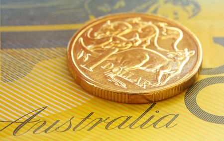 50 dollar bill: Australian one dollar coin on a fifty dollar note.  Close-up view, with shallow depth of field.