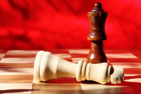 concede: Chess pieces in checkmate.  Wooden king and queen, with vibrant red background. Natural light.