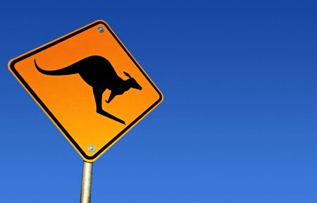 downunder: Kangaroo road warning sign, with brilliant blue Australian desert sky behind.  Clipping path included. Stock Photo