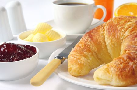 Continental breakfast with croissants, strawberry jam, butter curls, coffee and orange juice.   Stock Photo