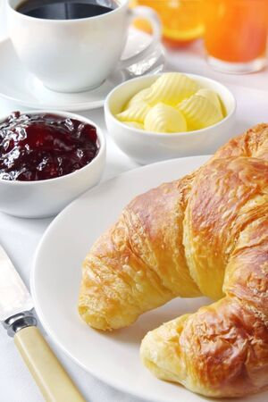 continental breakfast: Continental breakfast with croissants, strawberry jam and butter curls, fresh orange juice and coffee.