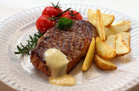 Grilled New York strip steak with bearnaise sauce, potato wedges, and cherry truss tomatoes.  Garnished with parsley and rosemary. photo