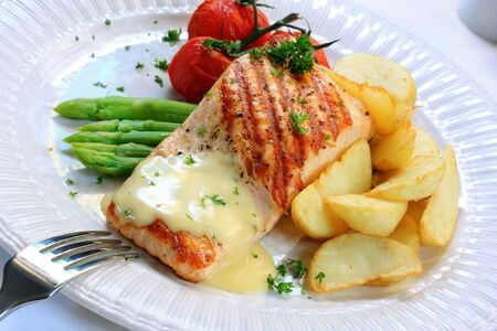 wedges: Meal of grilled salmon fillet, served with asparagus, potato wedges, truss tomatoes, and hollandaise sauce.