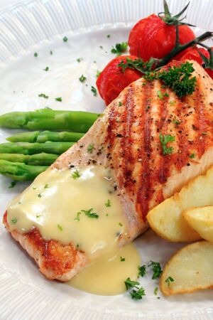 wedges: Meal of grilled atlantic salmon with potato wedges, roasted truss tomatoes, and hollandaise sauce.