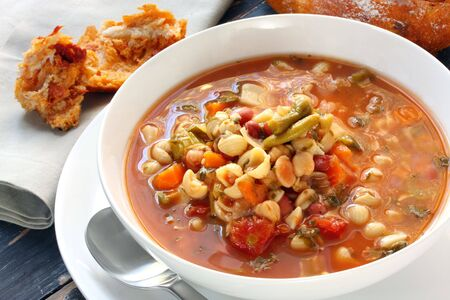 minestrone: Bowl of minestrone with fresh bread baked with sundried tomatoes. Stock Photo