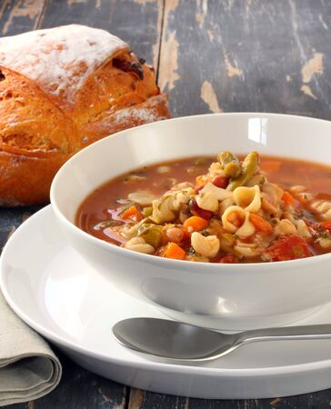 noodles soup: Minestrone pasta soup on rustic table, with fresh-baked cob of bread.