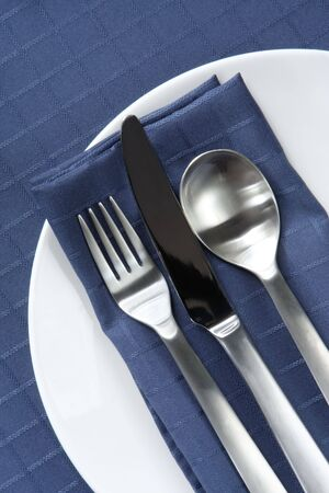 white napkin: Place setting with knife, fork and spoon on white plate, with navy blue linen.