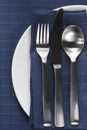 Place setting with cutlery on white plate, with navy blue napkin and tablecloth. photo