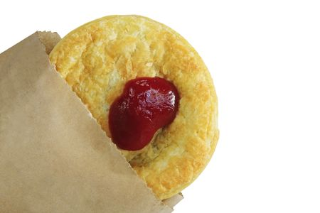 meat pie: Australian meat pie with tomato sauce, in a bag.  Traditional eating at Australian Rules Football games. Stock Photo