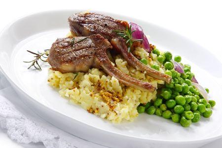 Gegrillte Lammkoteletts auf einem Bett aus Kartoffelpüree mit Samen Senf, Zucker-Snap frischen Erbsen und gegrilltem roten Zwiebeln. Garniert mit Rosmarin.