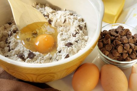 Baking chocolate chip cookies.  Mixing bowl with flour, eggs, chocolate chips and butter. Stock Photo - 3251332