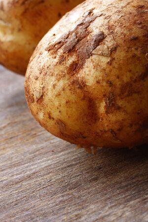 unwashed: Unwashed patate su un tagliere di legno. Profondit� di campo.