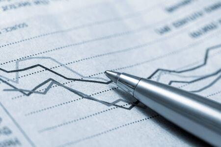 fluctuations: Ballpoint pen resting on stockmarket graph.  Blue tone.