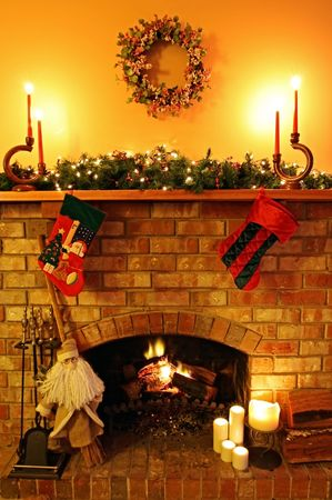 Open log fire, with Christmas candles, garland, broomstick Santa, and stockings Stock Photo