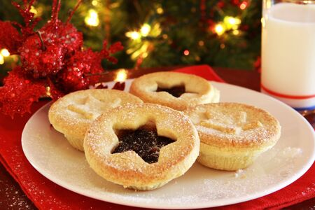 mince: Santas treats - plate of Christmas mince pies and glass of milk, with Christmas tree behind.
