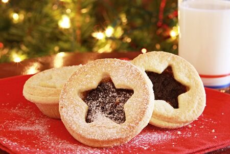 Santas treats - mince pies and a glass of milk, on red napkin with Christmas tree behind. photo