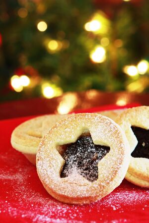 typically english: Christmas mince pies on a red napkin with Christmas tree behind.  Sprinkled with powdered sugar, waiting for .