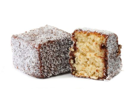 lamington: A lamington, isolated on white.  Traditional Australian sponge cake dipped in chocolate, then rolled in coconut.