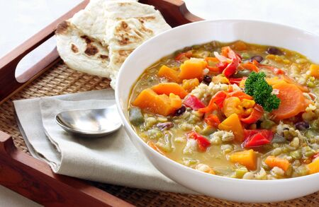 turkish bread: Vegetable soup with Turkish bread, on a tray.  A hearty, warming meal.