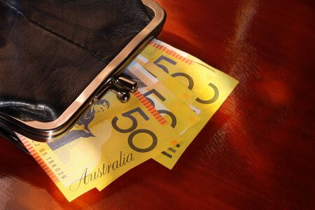 coin purse: Coin Purse with Australian fifty dollar notes.  Against polished timber, in mottled natural light. Stock Photo
