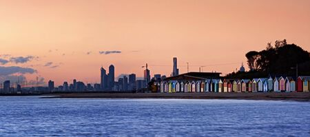 melbourne australia: Melbourne, Australia, viewed from Brighton Beach at sunset.  Bathing boxes in the foreground.   Stock Photo