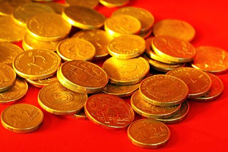 Golden Australian one and two dollar coins, scattered on red background. photo