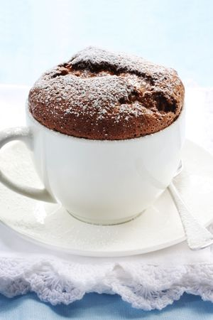 powdered sugar: Chocolate souffle served in a white coffee cup, dusted with powdered sugar. Stock Photo