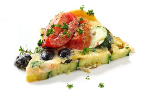 omelette: Wedge of vegetable frittata.  Italian style omelette, with roma tomatoes, zucchini (courgette) and black olives.  Garnished with parsley and thyme. Stock Photo