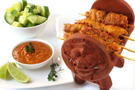 satay sauce: Satay chicken on a Balinese brasserie, accompanied by satay sauce, cucumber, lime and thyme.