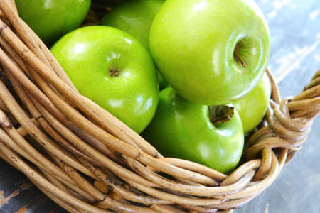 granny smith: Cane basket of granny smith apples, on rustic wooden table.