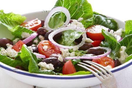 Greek salad in old enamel bowl, on wooden table. photo