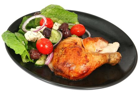 Roast chicken with a Greek salad, on a black plate, isolated on white.