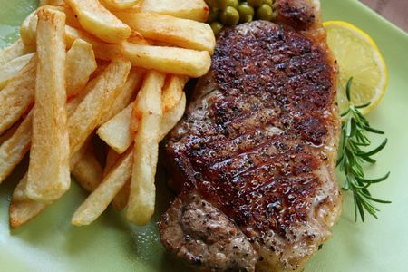 Grilled beef steak with chips (french fries) and peas.  Garnished with rosemary and lemon. Stock Photo - 3499457