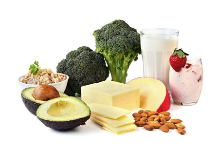 Food sources of calcium, isolated on white.  Includes milk, yogurt, almonds, cheeses, broccoli, salmon, and avocado. photo