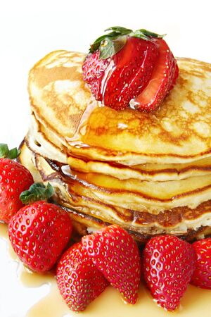 Stack of pancakes with fresh strawberries and maple syrup.  Close-up view of this indulgent meal.
