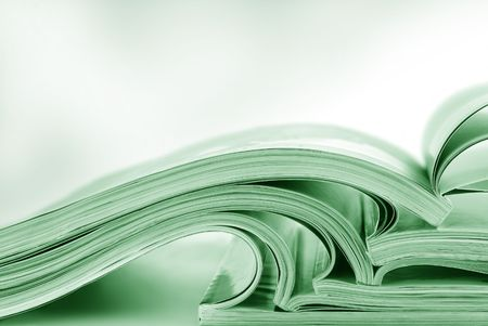 green tone: Stack of open magazines, in green tone.