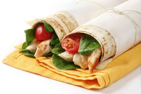 sandwich de pollo: Envolver bocadillos rellenos con pollo asado, hojas de espinaca y tomates cherry. Piso pan atadas con cuerdas y papel. Foto de archivo