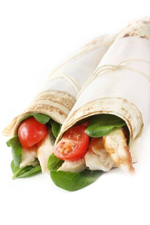 Wrap sandwiches with grilled chicken, spinach and cherry tomatoes.  Flat bread tied with paper and kitchen string. Stock Photo - 3544751