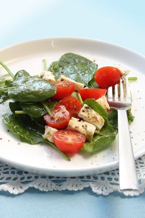 'baby spinach': Salad of baby spinach leaves, cherry tomatoes, and goats cheese, with a balsamic dressing.
