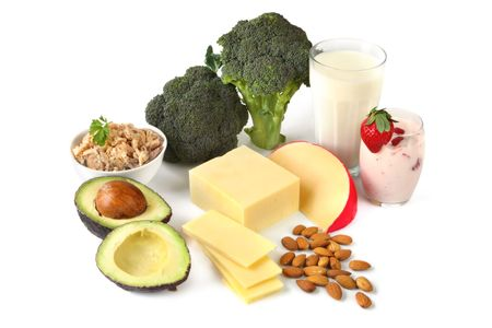 enriched: Calcium-rich foods, on white background.  Includes avocado, salmon, broccoli, milk, yoghurt, cheeses, and almonds.