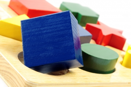 Square peg in a round hole.  Wooden block shapes, with square block over round hole. Stock Photo