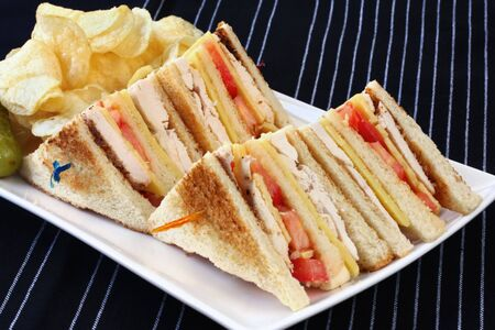 chicken sandwich: Club sandwiches served with potato chips and a pickle.