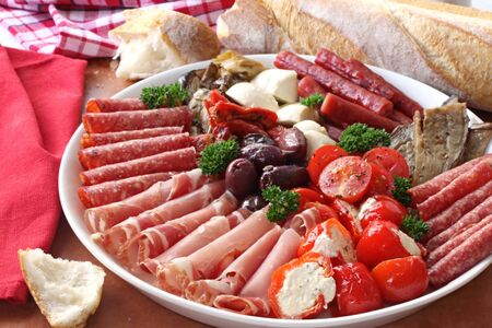 Platter of antipasto, with crusty bread.  A mixture of salami, prosciutto, bocconcini, grilled peppers stuffed with goats cheese, eggplant, tomatoes, and olives. photo