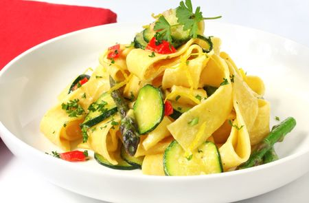 ribbon pasta: Pappardelle (wide ribbon pasta) with courgette and asparagus and a creamy sauce. Stock Photo