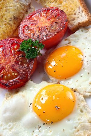 Breakfast of fried eggs, tomatoes and wholewheat toast.